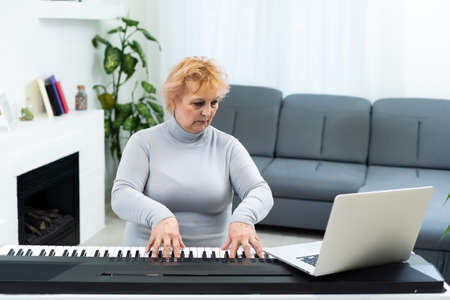 elderly woman learning to play synthesizer on laptop online at home