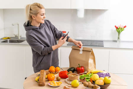Woman sorts out purchases in the kitchen. Grocery delivery in paper bags. Subscription service from grocery store in conditions of quarantine because of coronavirus COVID19