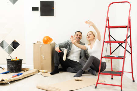 Happy couple having fun painting their apartment