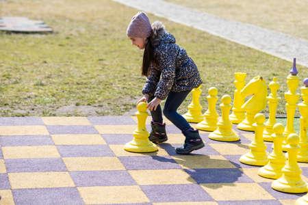 little girl playing big chess