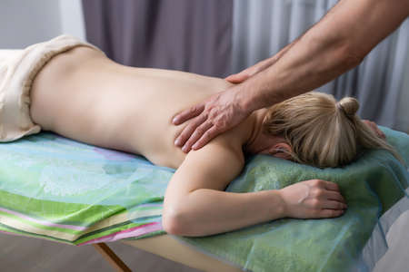 Cute chubby woman getting a back massage at home Stock Photo