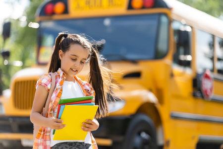 Little girl standing by a big school bus door with her backpack.