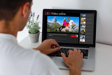 watching a video about a trip online by laptop
