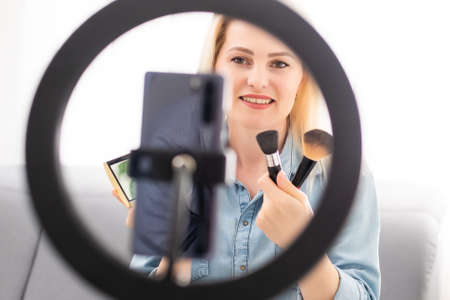 blogger woman records video with round lamp