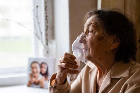 Close-up portrait of an elderly woman in a medical breathing mask. Foto de archivo