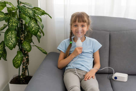 sick little girl makes inhalation over grey background with copy space. Girl making inhalation with nebulizer at home. child asthma inhaler inhalation nebulizer steam sick cough