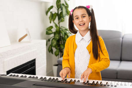 a little girl learns to play the synthesizer. learning to play musical instruments.