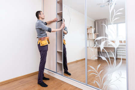 Closet Cabinets Contractor. Finishing Wooden Wardrobe by Professional Installer. Stock Photo