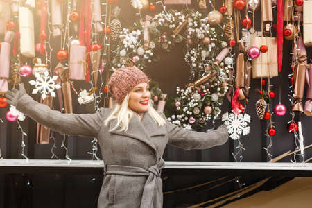 woman on street looking at shop windows decorated for Christmas