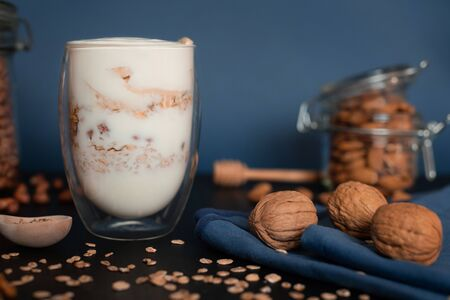 Yogurt with oatmeal and walnuts, almonds and peanuts with honey in a clear glass with double walls on a dark blue