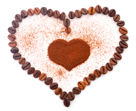 Textured background macro of fresh coffee beans in the shape of a heart.