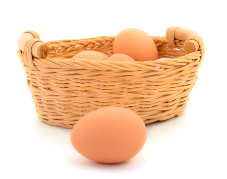 Fresh brown eggs in basket isolated on white background.