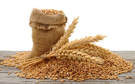 A bag of grain and wheat bran on a wooden background. Stok Fotoğraf