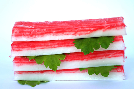 crabmeat: pile of crab sticks and celery  leaf isolated on white background