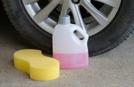 valeting: cleaning shampoo and sponge on car tire background