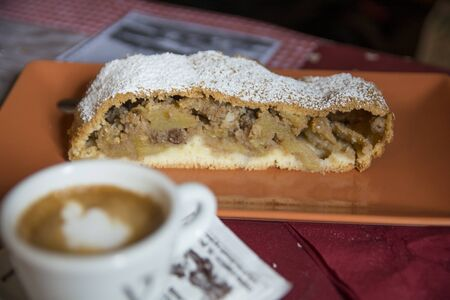 A slice of traditional Apple Strudel, powdered with sugar, served on a plate next to a cup of coffee 写真素材