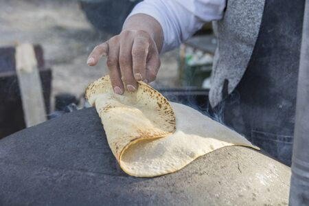 Man baking a traditional Druze Pita bread, on a Saj or Tava
