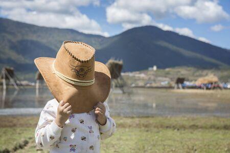 Chinese child hiding his face with a cowboy hat, at the Na Pa lake, Shangri-La, Yunnan, China