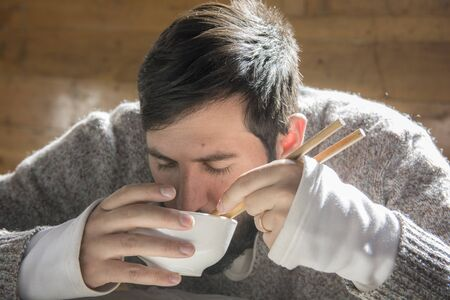 Portrait of a bearded man seating and eating from a bowl ,using chopsticks, in a wooden cabin.