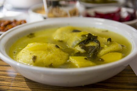 Traditional hot yellow Kubbe soup, a famous middle eastern dumplings soup dish, served in a bowl. Jerusalem, Israel.