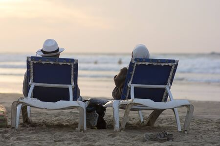 Man and woman sitting and relaxing together on the beach and watching the beautiful sunset, Tel Aviv, Israel