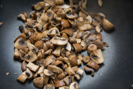 Close up view of sauteed slices of Common Mushrooms (Agaricus bisporus) cooking in the pan