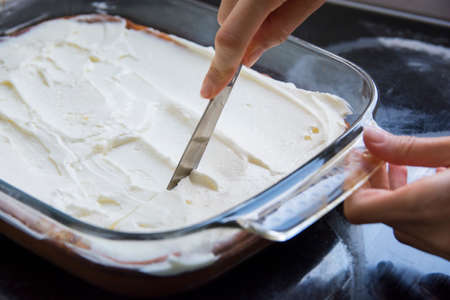 Woman hand cutting with a knife a baked cheese cake with whipped cream topping