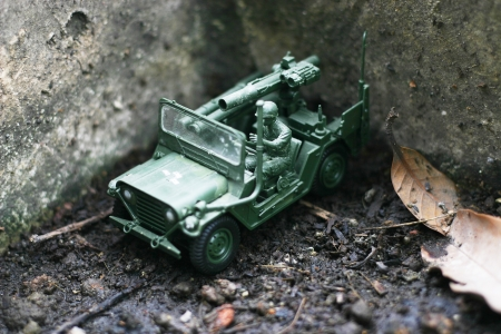 A toy soldier with jeep on his mission in the forest garden  photo
