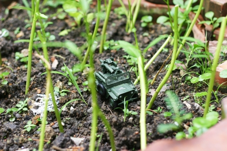 A toy soldier with jeep on his mission in the forest garden  Stock Photo