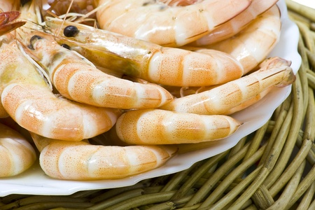 Close up boiled shrimp with shell on plate and basket