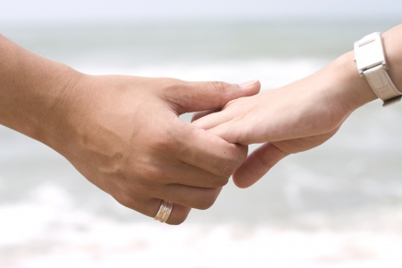 couple holding hands: Hand Holding in Sea Background