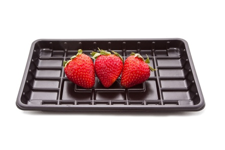 Strawberry group in the black plastic tray isolated on white Stock Photo