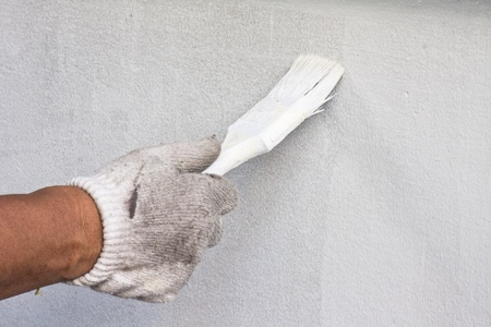 Hand hodling paint brush against the wall