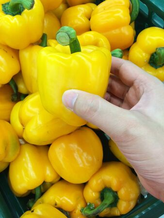 Yellow peppers with asian man hand