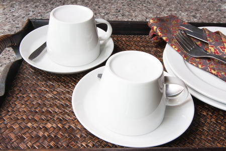 Coffee cup, knife, fork, plate on wooden tray