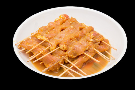 Raw marinated meat in plate for pork bbq skewer on black background