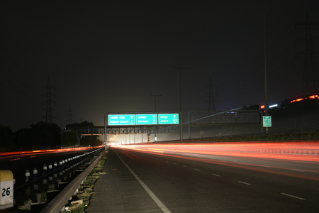 haryana: Speeding cars on modern Road infrastructure in Gurgaon, Delhi, India. Artistic long exposure shot at night Stock Photo