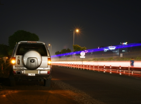 gurgaon: Gurgaon, India:August 19th,2015:Legendry Tata Safari SUV on an urban road in Gurgaon with light trails of cars and bus lights with other high rise buildings on the side of road,artistic low light shot