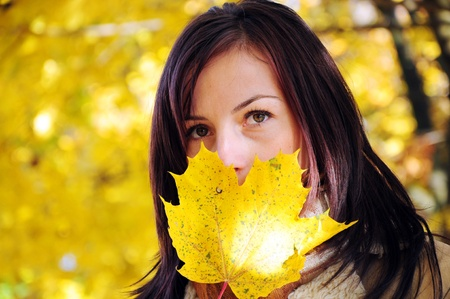 Close-up portrait of attractive young woman with maple tree leaf Banco de Imagens