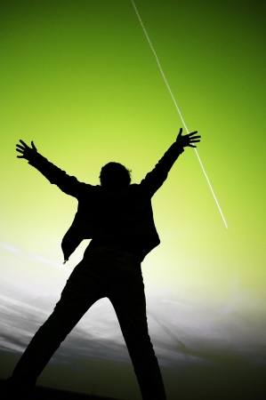 worship praise: silhouette of a woman raising her arms out to the sky Stock Photo