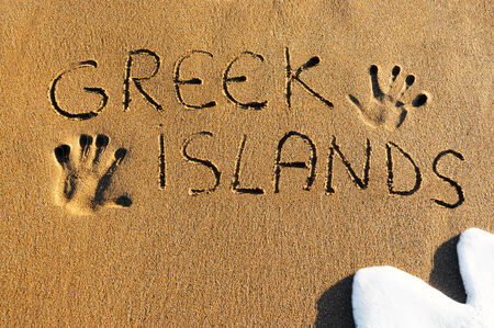 Greek islands written on sandy beach Banco de Imagens