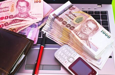 calculated: Stock Photo - close up of 1000 baht banknotes and mobile phone on note book