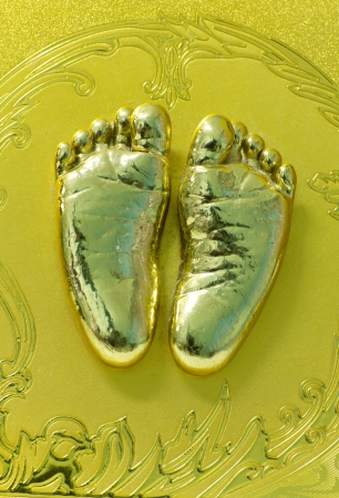 Stock Photo - Little child's foot gold print in Plaster
