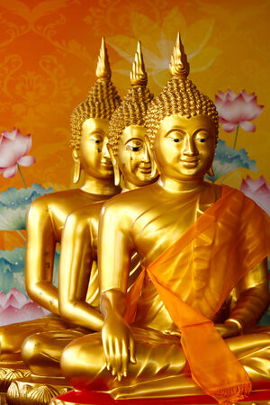 Row of sitting golden Buddha statutes photo