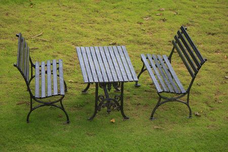 black shabby chic cast iron patio outdoor furniture set on grass lawn Stock Photo photo
