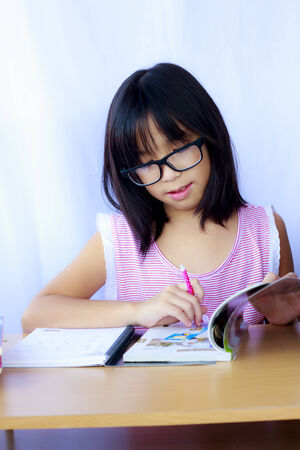Stock Photo - Portrait of cheerful Asian young girl doing her homework photo