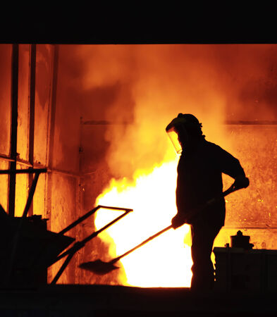 steel factory: steel worker takes a sample from oven Stock Photo
