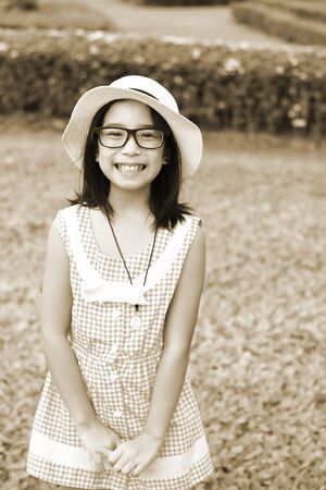 southeast asian ethnicity: Vintage portrait of beautiful little girl touching her hat Stock Photo