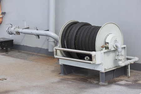 long range: high pressured hose and reel distributes water at a long range. Stock Photo