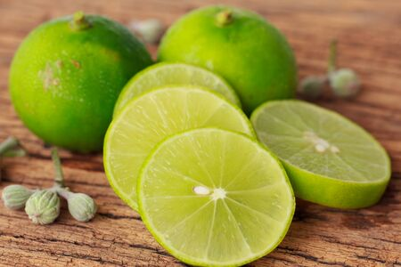Fresh green lime on old wooden background photo